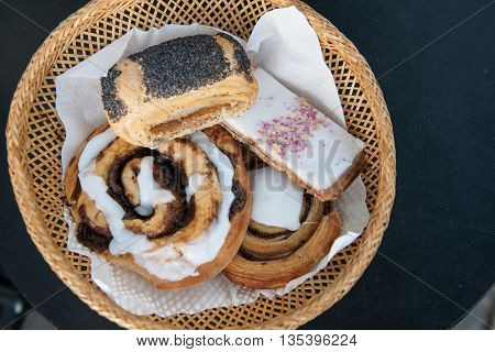 Tasty Danish pastry and cakes in a basket on a table stock picture