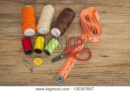 Sewing background. Accessories for needlework on wooden background. Spools of thread scissors buttons measuring tape sewing supplies. Set for needlework top view with copy space. poster