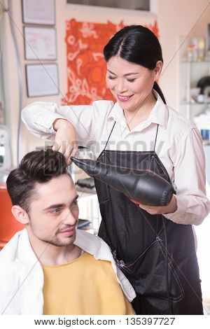 Picture of handsome man having his hair dry in hairdressing salon. Hair stylist or barber girl drying man's hair with hair dryer.