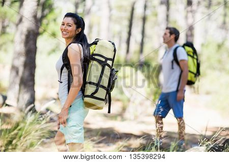 Woman smiling and posing with a backpack on the wood