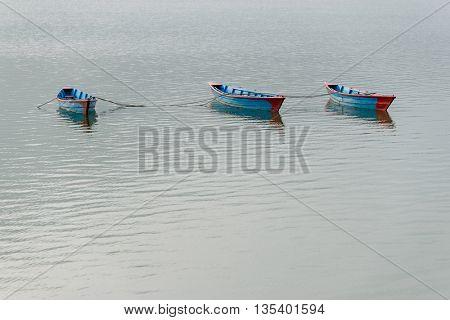 Three blue small boats on Phewa Lake in Pokhara, Nepal