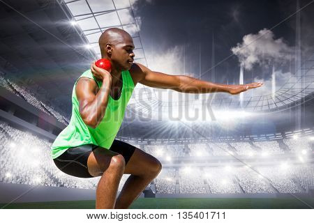 Sportsman practising the shot put against sports arena