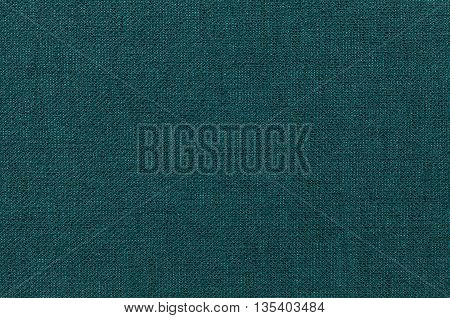 Dark green background from a textile material. Fabric with natural texture. Cloth backdrop.