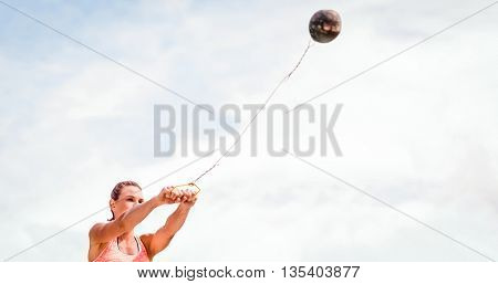 Portrait of sportswoman practising hammer throw against blue sky with clouds
