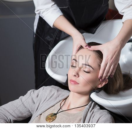 Unrecognizable professional hairdresser washing hair to her client. Beautiful hairdresser washing hair to her client lady in hairdressing salon. Client sitting with her eyes closed.