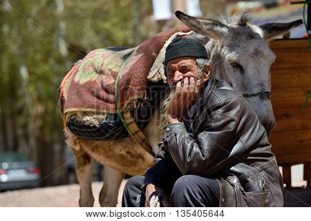 ABYANEH - APRIL 20: Unknown old man resting in a street in Abyaneh, Iran on April 20, 2015. Abyaneh is small mountain village, at the 2006 census, its population was 305, with 160 families.
