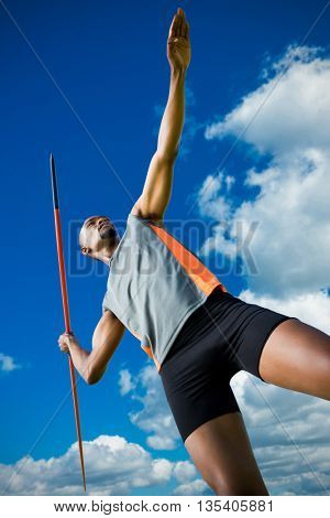 Low angle view of athletic man preparing his javelin throw against low angle view of blue sky