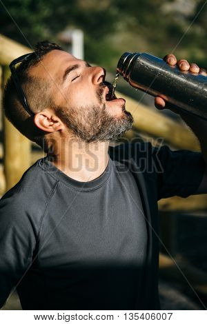 Portrait of thirtsty traveler drinking from flask in sunlight with eyes closed