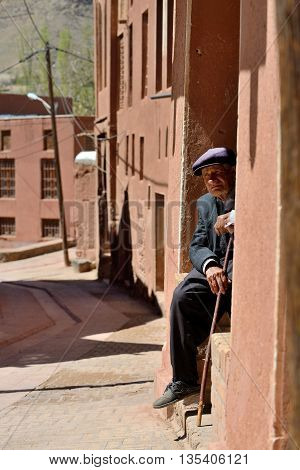 ABYANEH - APRIL 20: Unknown old man resting in a street in Abyaneh, Iran on April 20, 2015. Abyaneh is small mountain village, at the 2006 census, its population was 305, in 160 families.