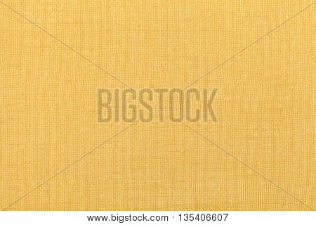 Light yellow background from a textile material. Fabric with natural texture. Cloth backdrop.