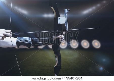 Close up of someone practising archery against football pitch with bright lights