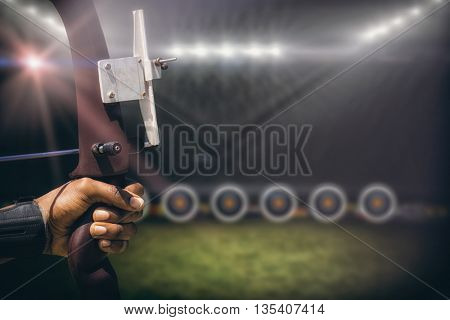 Focus on hand doing archery against football pitch with lights