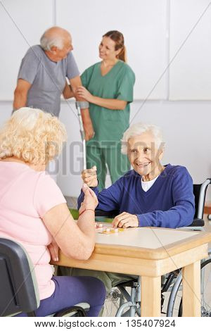Two senior people playing Bingo together in a nursing home