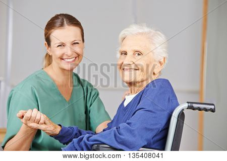 Geriatric nurse and senior woman in wheelchair smiling together in nursing home