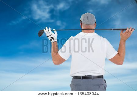 Rear view of golf player holding a golf club against blue sky