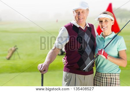 Couple golf players looking the camera against view of a golf course