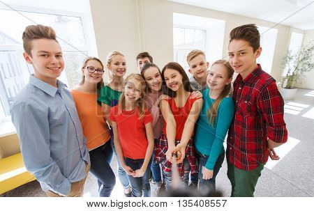 education, school, technology and people concept - group of happy smiling students taking picture with smartphone selfie stick in corridor