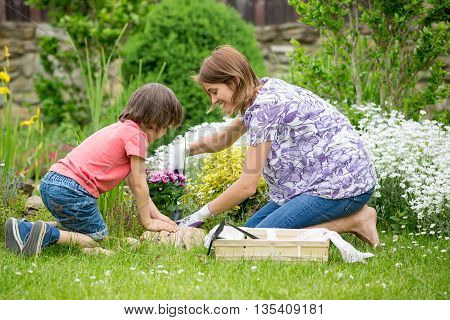 Mother And Son Gardening Together In Their Little Garden