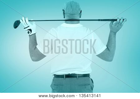 Rear view of golf player holding a golf club against blue vignette background