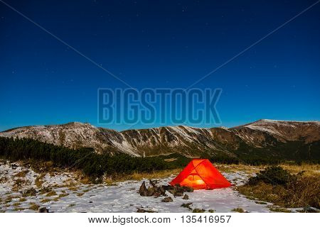 Winter Hiking Bivouac in Mountain Landscape and Night Sky with Many Stars Red Tent and Snowy Terrain