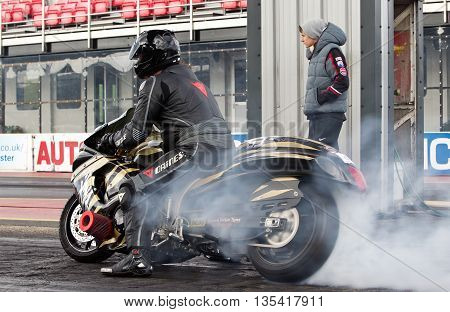 PODINGTON, UK - OCTOBER 19: An unnamed rider warms the tyres of his race bike before racing down the Santa Pod raceway during the Extreme Performance Bike event on October 19, 2014 in Podington