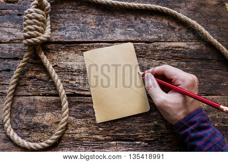man writes a suicide note on a wooden background