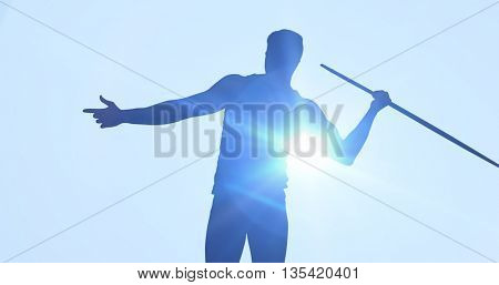 Rear view of sportsman practising javelin throw against blue background