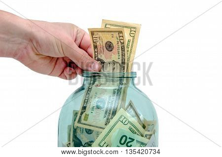 man's hand puts the US currency in a jar of glass,isolated on white background