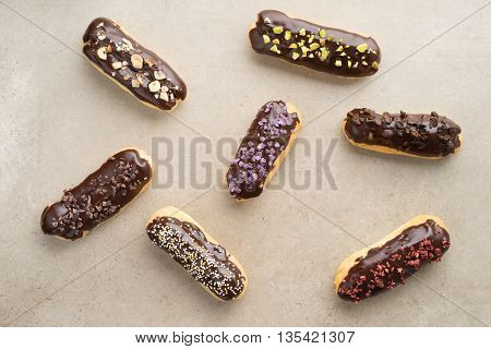 Eclairs with chocolate ganache with different toppings