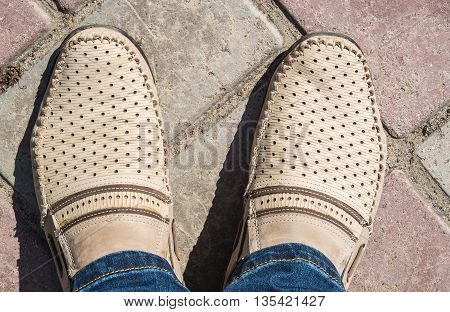 Beige moccasins on their feet close up