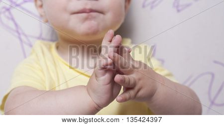 Baby boy clapping after drawing with wax crayon a plasterboard wall