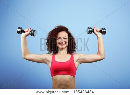 Attractive woman exercising with dumb bells on blue background
