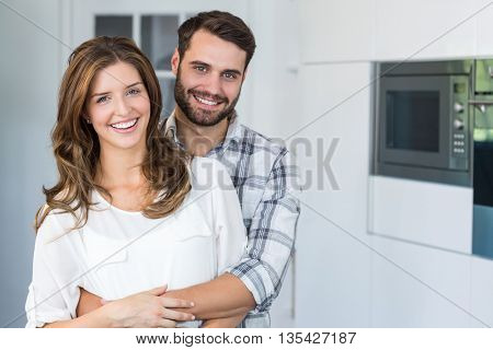 Close-up portrait of happy young couple embracing at home