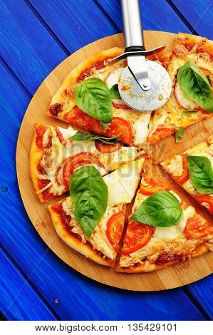 Cutted margherita pizza with round knife and basil vertical overhead view