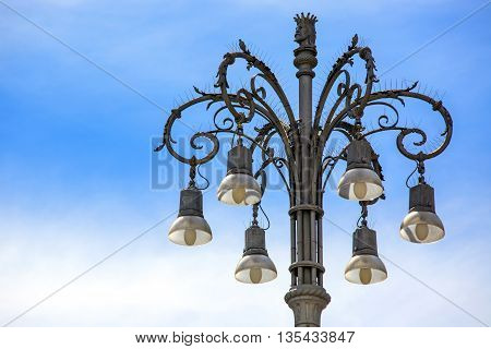 Beautiful old streetlamp with blue sky background. Place for text.