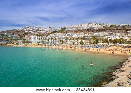PUERTO RICO, SPAIN - APRIL 21, 2016: Beach of Puerto Rico with many tourists, Gran Canaria. Puerto Rico is a specially constructed holiday resort situated on the south-west coast of Gran Canaria.