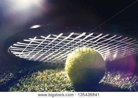Close up of tennis ball under a racket on grass