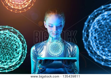 Futuristic cyber young woman in silver clothing holding lighting panel in her hands with glowing polygonal abstract sphere with abstract spheres at background