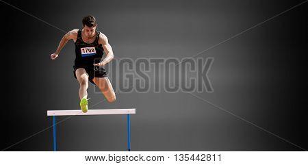 Sportsman practising hurdles against black background