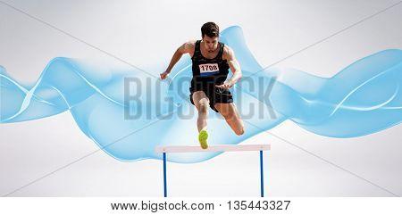 Sportsman practising hurdles against blue wave