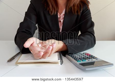 Woman hands pain on desk office syndrome concept with notebook and calculator concept
