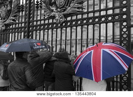 LONDON ENGLAND - OCTOBER 21, 2015: Tourists looking through a gate of Buckingham palace on a rainy day. Buckingham palace is the official residence of Queen Elizabeth II