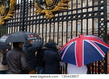 LONDON ENGLAND - OCTOBER 21: Tourists looking through a gate of Buckingham palace on a rainy day. Buckingham palace is the official residence of Queen Elizabeth II