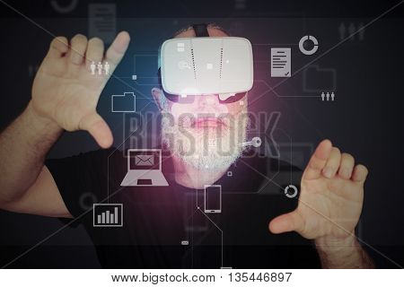 Aged bearded man in 3d virtual reality glasses over dark background is zooming the virtual reality screen with his hands