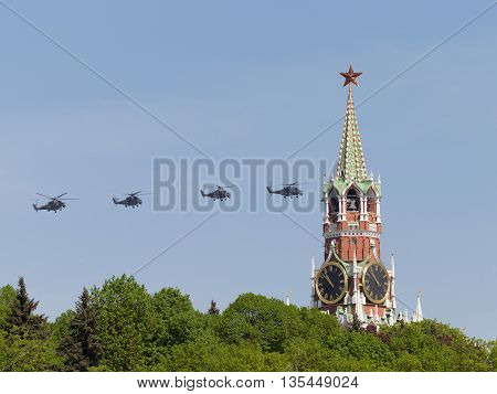 Moscow - May 9 2016: Four gray military helicopters Mi-35 flying on the background of the Spasskaya Tower of the Kremlin during Victory Day parade May 9 2016 Moscow Russia