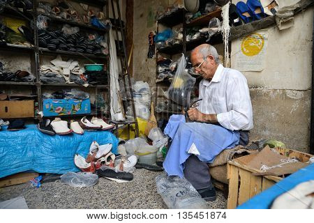 SHIRAZ - APRIL 14: Unknown man repairs shoes in a market (Vakil Bazaar) in Shiraz Iran on April 14 2015. Vakil Bazaar is the most important tourist attraction in Shiraz Iran.
