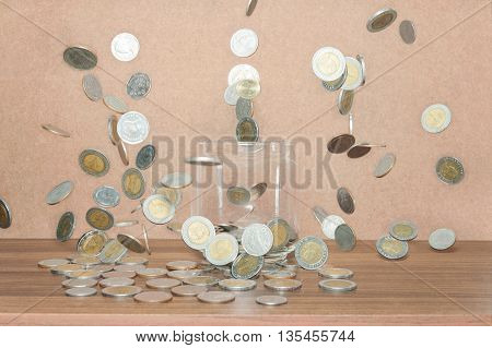Close up of glass bottle stacking silver coins falling on wooden table, Vintage style