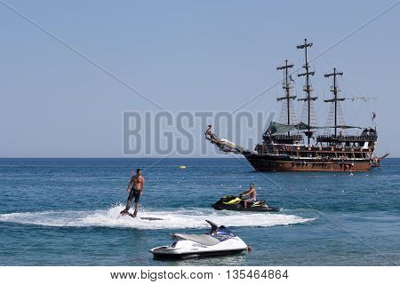CAMYUVA KEMER TURKEY - JULY 16 2015: On the coast of Turkey along with the traditional personal watercraft are becoming popular flyboard and yachting stylized pirate schooner