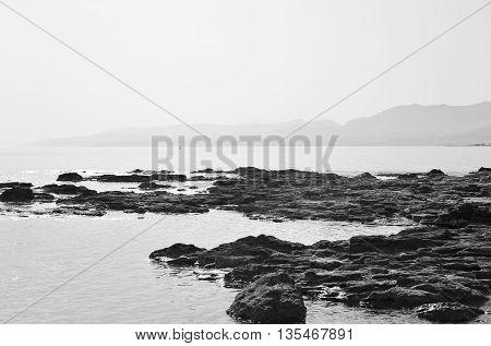 Rocks on the coast of Cretan Sea near Hersonissos Crete Greece. Black and white.