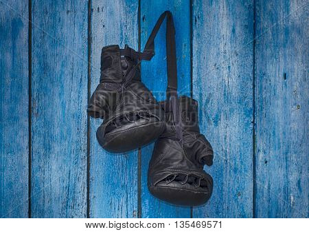 pair of black gloves for Thai boxing hanging on a nail in the old blue wooden wall